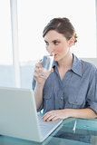 Gorgeous young businesswoman drinking a glass of water sitting at her desk