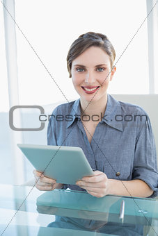 Beautiful businesswoman holding her tablet sitting at her desk