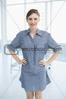 Beautiful businesswoman posing in office with hands on hips