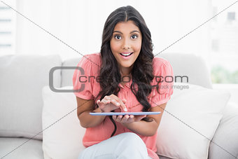 Excited cute brunette sitting on couch holding tablet