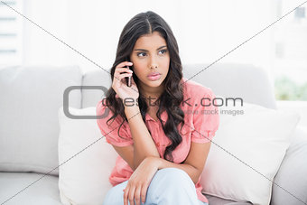 Thoughtful cute brunette sitting on couch phoning