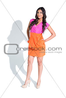 Smiling attractive brunette posing and standing hands on hips