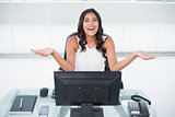 Laughing cute businesswoman sitting behind desk