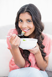 Gleeful cute brunette sitting on couch holding salad bowl