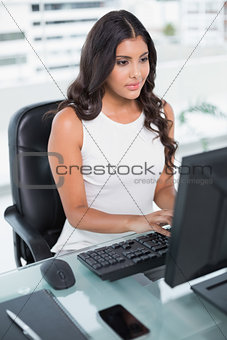 Calm cute businesswoman working at computer