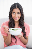 Pleased cute brunette sitting on couch holding salad bowl