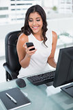 Smiling cute businesswoman holding smartphone