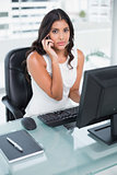 Unsmiling cute businesswoman phoning on smartphone
