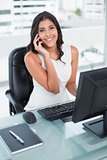 Cheerful cute businesswoman phoning on smartphone