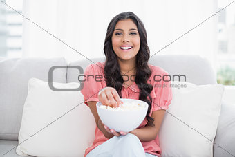 Cheerful cute brunette sitting on couch holding popcorn bowl