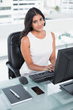 Content cute businesswoman working at computer