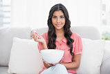 Pleased cute brunette sitting on couch holding popcorn bowl