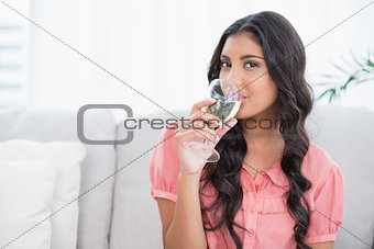 Happy cute brunette sitting on couch drinking white wine