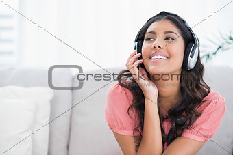 Content cute brunette sitting on couch listening to music