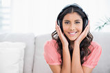 Happy cute brunette sitting on couch listening to music