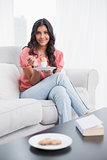 Smiling cute brunette sitting on couch holding hard boiled egg