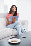 Happy cute brunette sitting on couch holding tablet