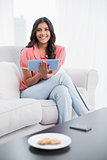 Smiling cute brunette sitting on couch holding tablet
