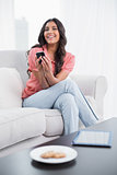 Happy cute brunette sitting on couch using smartphone