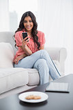 Smiling cute brunette sitting on couch using smartphone