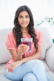 Content cute brunette sitting on couch holding glass of juice