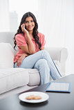 Content cute brunette sitting on couch phoning on smartphone