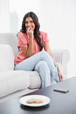 Happy cute brunette sitting on couch eating red apple