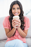 Cheerful cute brunette sitting on couch holding disposable cup