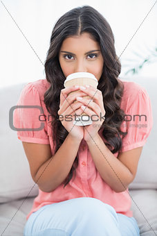 Calm cute brunette sitting on couch drinking from disposable cup