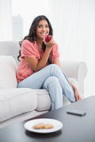 Happy cute brunette sitting on couch holding red apple