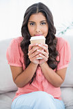 Calm cute brunette sitting on couch holding disposable cup