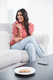 Smiling cute brunette sitting on couch holding red apple