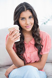Content cute brunette sitting on couch holding disposable cup