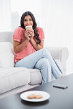 Smiling cute brunette sitting on couch holding disposable cup