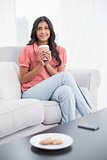 Pleased cute brunette sitting on couch holding disposable cup