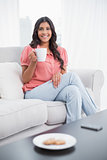Smiling cute brunette sitting on couch holding mug