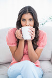 Calm cute brunette sitting on couch holding mug