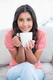 Content cute brunette sitting on couch holding mug