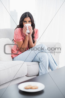 Calm cute brunette sitting on couch drinking from mug