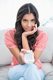 Content cute brunette sitting on couch holding remote