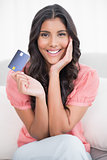 Smiling cute brunette sitting on couch showing credit card