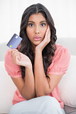 Shocked cute brunette sitting on couch showing credit card