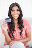 Happy cute brunette sitting on couch showing credit card