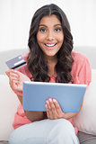 Happy cute brunette sitting on couch holding credit card and tablet