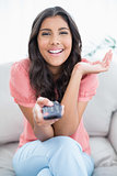 Gleeful cute brunette sitting on couch holding remote