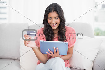 Smiling cute brunette sitting on couch holding credit card and tablet