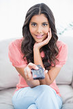 Amazed cute brunette sitting on couch holding remote