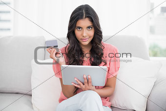 Calm cute brunette sitting on couch holding credit card and tablet