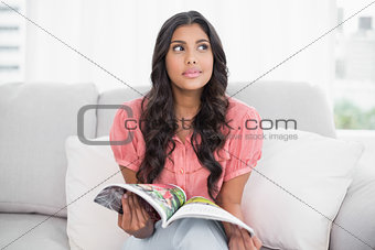 Thoughtful cute brunette sitting on couch holding magazine