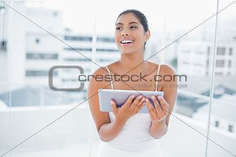 Laughing toned brunette holding tablet